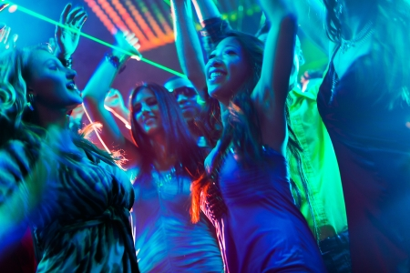 nightclub crowd: Group of party people - men and women - dancing in a disco club to the music
