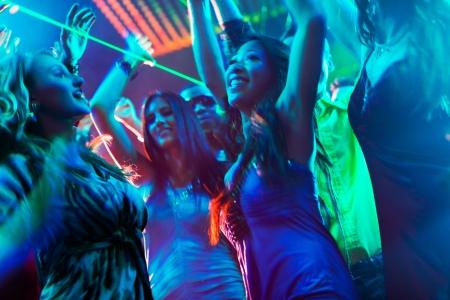 night club: Grupo de gente del partido, hombres y mujeres - bailando en una discoteca con la m�sica Foto de archivo