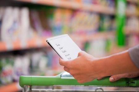carro supermercado: Mujer la celebración de los compradores lista de verificación con el carro en el supermercado