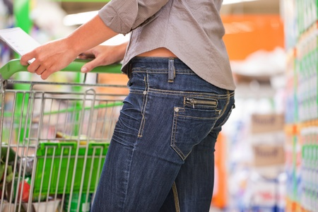 Trendy young woman shopping with trolley at supermarket Stock Photo - 13453071