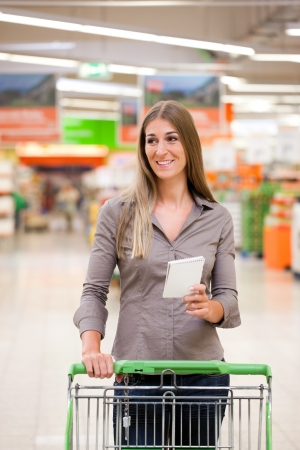 Smiling young woman shopping with trolley and checklist photo