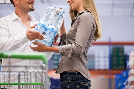 Happy young couple shopping for pure packed bottles at supermarket photo