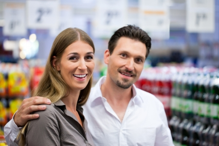 Happy couple smiling while shopping at supermarket photo
