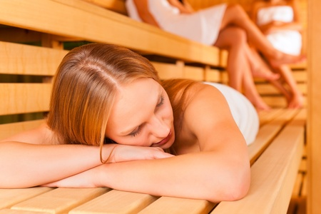 woman towel: Sauna wellness - young happy women, presumably friends, in Spa, one girl resting on bench in front Stock Photo