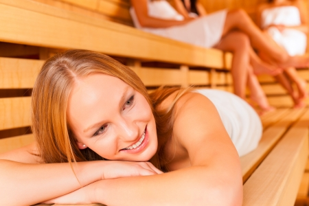 Sauna wellness - young happy women, presumably friends, in Spa, one girl resting on bench in front photo