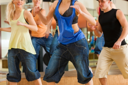Zumba or Jazzdance - young people dancing in a studio or gym doing sports or practicing a dance number Stock Photo - 13453018