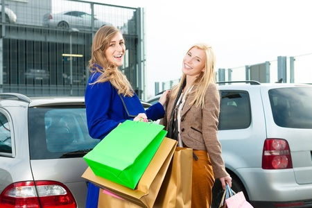 Two women were shopping in a mall or shopping centre and driving home now with their car Stock Photo - 13452868