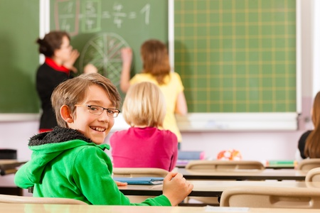 elementary student: Education - Young female teacher with pupil in his form of the elementary or primary school teaching