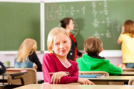 Education - Young female teacher with pupil in his form of the elementary or primary school teaching Stock Photo - 13452993