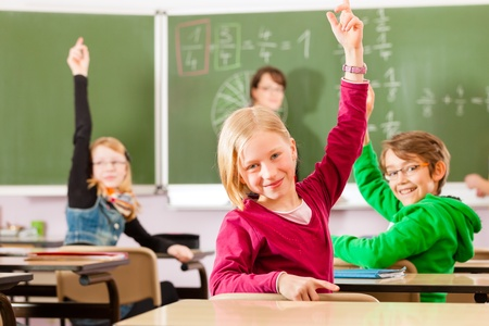 elementary kids: Education - Young female teacher with pupil in his form of the elementary or primary school teaching