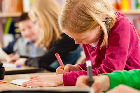 Education - Pupils at primary or elementary school doing their homework or having a school test Stock Photo - 13453055