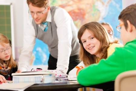 Education - Pupils and teacher learning at elementary or primary school in the classroom Stock Photo - 13452846