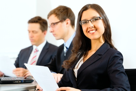 one on one meeting: Business people sitting in a meeting or workshop in an office, one woman is looking into the camera