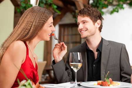 dinner date: Happy young man feeding woman at the restaurant table