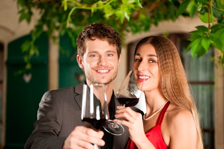 Portrait of happy couple celebrating an occasion having red wine photo