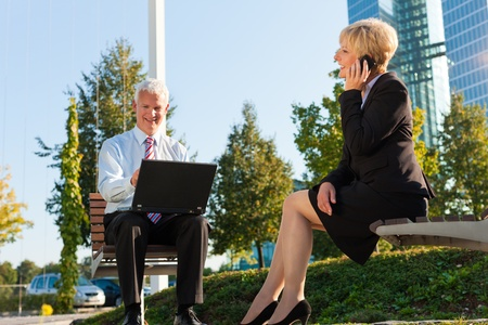 he and she: Business people working outdoors - he is working with laptop, she is calling someone Stock Photo
