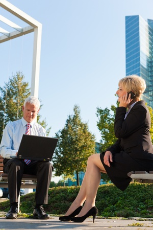 Business people working outdoors - he is working with laptop, she is calling someone on phone photo