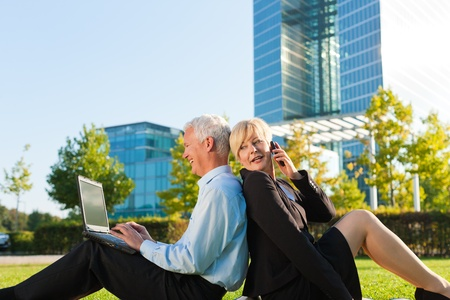 Business people working outdoors on a meadow - he is working with laptop, she is calling someone on phone photo