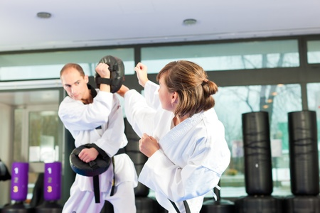 martial arts woman: People in a gym in martial arts training exercising Taekwondo, both have a black belt