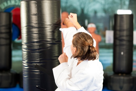 People in a gym in martial arts training exercising Taekwondo, he is the trainier or master photo