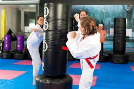 he: People in a gym in martial arts training exercising Taekwondo, he is the trainier or master