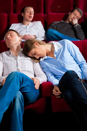 comedic: Couple and other people, probably friends, in cinema watching a movie, it seems to be a boring movie