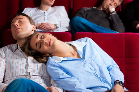 theater audience: Couple and other people, probably friends, in cinema watching a movie, it seems to be a boring movie