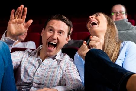 riendo: Pareja y otras personas, probablemente sus amigos, en el cine viendo una película, que parece ser una película divertida