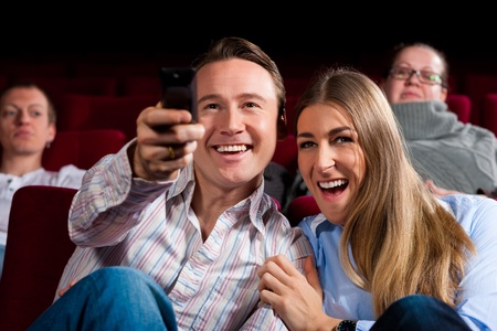 Couple and other people, probably friends, in cinema watching a movie, they try to switch to another program that is not possible in a cinema photo