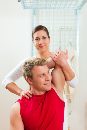 therapists: Patient at the physiotherapy doing physical exercises with his therapist
