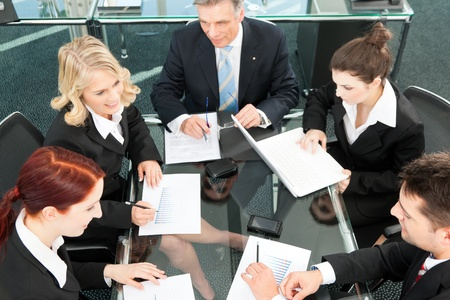 Business people - meeting in an office, the businesspeople are discussing a document photo
