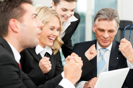 team building: Business people - team meeting in an office with laptop, the boss with his employees is obviously successful