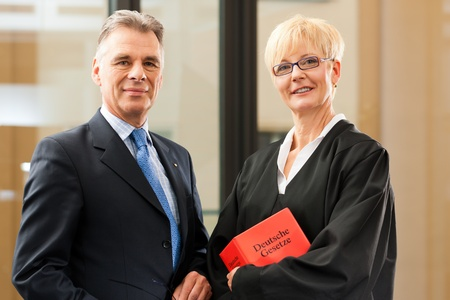 court room: Female lawyer with German civil law code and client in a court room
