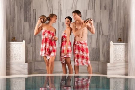 Three friends - two women, one man - doing wellness in the sauna of a thermal bath Stock Photo - 13503295