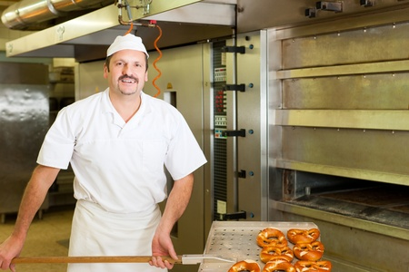 baker standing in his bakery in the morning and is baking bread or buns photo