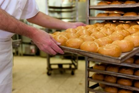 bread shop: panettiere in piedi nella sua panetteria al mattino e alla produzione di pane o focacce Archivio Fotografico