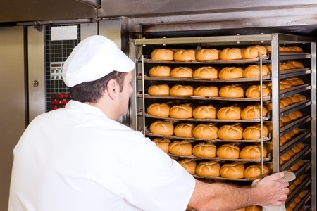 oven tray: baker standing in his bakery in the morning and is baking bread or buns