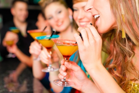 drinking straw: Young people in club or bar drinking cocktails and having fun Stock Photo