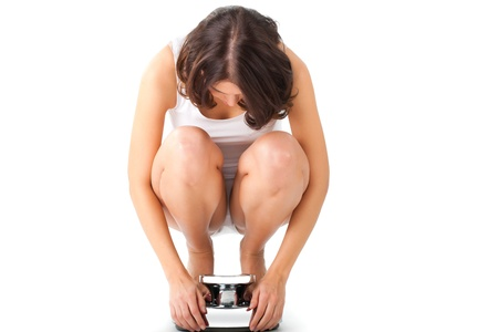 Diet and weight, young woman sitting on her haunches on a scale photo