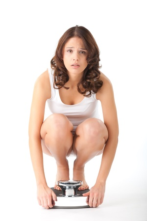 bulimia: Diet and weight, young woman sitting on her haunches on a scale