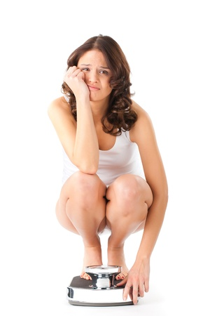 scale weight: Diet and weight, young woman sitting on her haunches on a scale