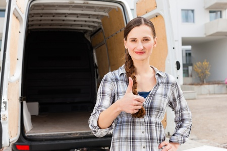 Young woman in front of moving truck, the van is still empty photo