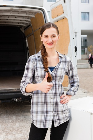 moving truck: Young woman in front of moving truck, the van is still empty