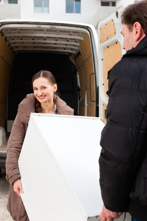 Young couple loading furniture into a moving truck, it is a fridge photo