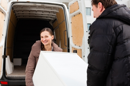 shipper: Young couple loading furniture into a moving truck, it is a fridge