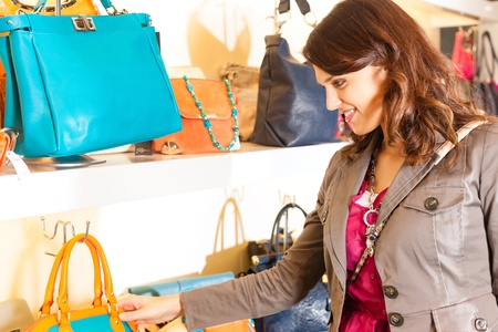 boutique shop: Young happy woman having fun while shopping in a mall, she is looking for a bag