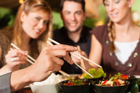 chinese meal: Young people eating in a Thai restaurant; they eating with chopsticks