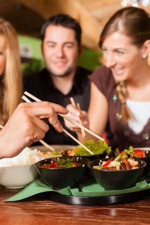personas comiendo: Los jóvenes que comen en un restaurante tailandés; que comer con palillos