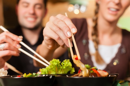 Young people eating in a Thai restaurant; they eating with chopsticks photo