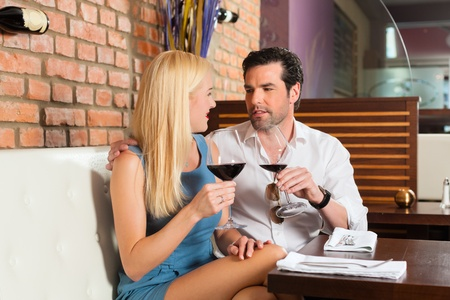 Attractive young couple drinking red wine in restaurant or bar, it might be the first date photo